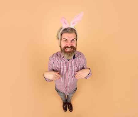 Easter party. Egg hunt. Rabbit man. Easter celebration concept. Man in bunny ears. Easter man. Bearded guy in bunny mask. Man in rabbit ears. Springtime. Holidays. Preparation for Easter. Full height