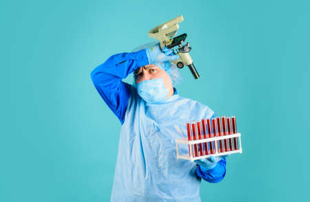 Scientist with test tubes with blood sample making research. Doctor analyzing blood sample in clinic. Laboratory technician with blood test tubes and microscope. Science, biology and medicine concept
