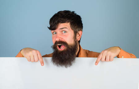 Copy space. Advertising. Bearded man with blank board. Space for text. Man holds empty board. Advertising banner. Man shows empty board. Ready for your text
