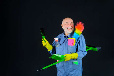 House cleaning. Cleaning time. Smiling man in uniform with cleaning equipment. Domestic service. Professional cleaning. Clean up. Clearing tools. Broom. Dust brush. Household. Housekeeping Stok Fotoğraf - 162232425