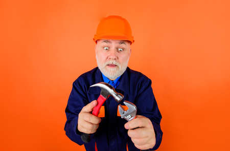 Hammer and spanner. Business, building, industry, technology. Repairment tools. Wrenches. Spanner. Portrait of mechanical worker. Man builder. Surprised builder in construction helmet. Hard hat Stok Fotoğraf