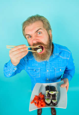 Sushi. Japan. Bearded man eating sushi. Hipster eating sushi rolls. Sushi delivery. Japanese food. Pickled ginger. Plate of maki rolls. Susi. Exotic nutrition. Sea food Stok Fotoğraf - 162232994