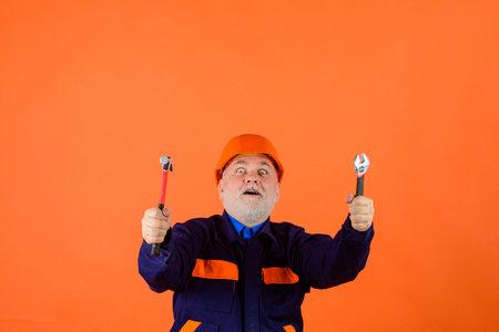 Building. Industry. Old man in construction helmet. Builder with repair tools. Engineers working. Repairment. Portrait mechanical worker. Construction worker in hardhat. Repair tools Stok Fotoğraf