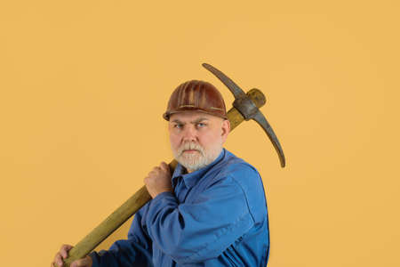 Builder man holds pickaxe. Craftsman working with pickaxe. Man holding pick-ax. Male miner worker in coveralls with pickaxe. Construction and building works. Bearded man in uniform holds pick ax Stok Fotoğraf