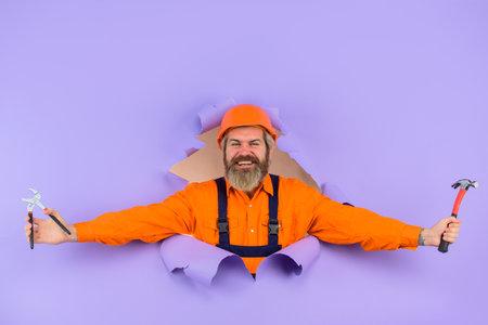 Advertising. Repair. Through paper. Bearded builder look through paper. Bearded man with repair tools. Hammer and nails. Excited repairman. Worker in helmet. Engineer