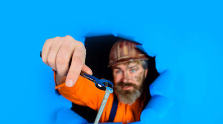Through paper worker in protective helmet. Builder holds wrenches. Repairing tools. Spanner. Bearded builder man with wrenches looking through paper. Man builder with wrenches looking through paper