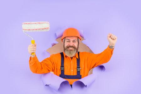 Through paper. Bearded builder look through paper. Painter. Bearded painter with paint roller. Excited repairman. Worker in helmet. Engineer Stok Fotoğraf - 162233254