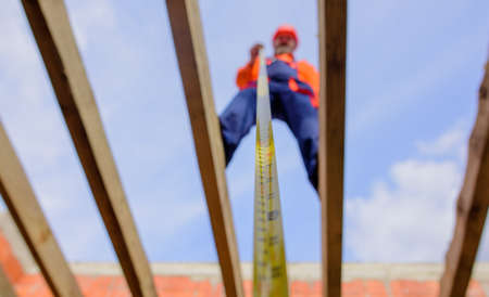 Builder with tape measure. Selective focus. Construction worker on construction site with roulette. Roofer carpenter in helmet with meter. Worker use tape measure. Builder equipment. Measuring device