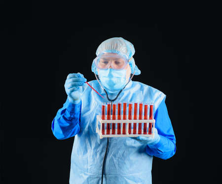Doing research in medical laboratory. Lab technician assistant analyzing blood sample in test tubes at laboratory. Scientist holds rack with test tubes and pipette. Laboratory researcher concept