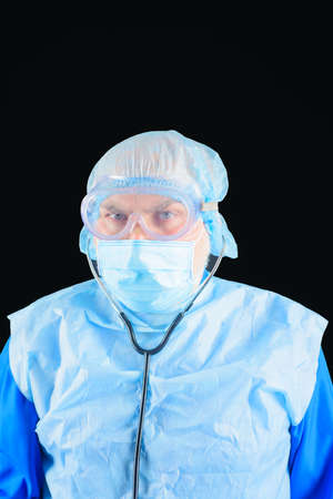 Doctor with stethoscope. Healthcare, profession and medicine concept. Handsome doctor in medical uniform with stethoscope. Medical physician doctor man. Man doctor in protective suit and medical mask Stok Fotoğraf