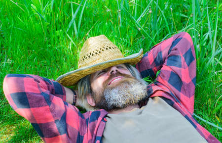 Bearded man lying on grass. Happy man relaxing on green grass outdoors in summer. Happy relaxed male in checkered shirt and hat lying on green grass. Enjoying sunny day. Unity with nature