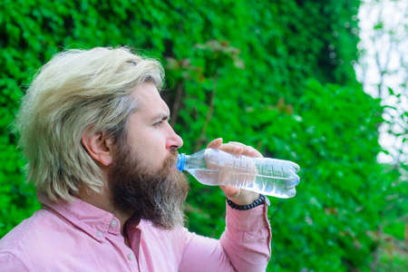 Bearded man drinking water. Hydration concept. Aqua. Dehydration. Man drink water outdoor. Man with water bottle. Healthy lifestyle. Health care concept. Drinking water. Drink