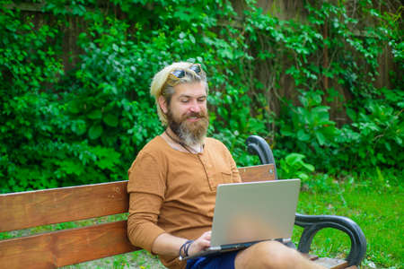Man sitting outside with laptop. Freelance. Man with laptop at park. Smiling man working on laptop outdoors. Study and work online. Online work