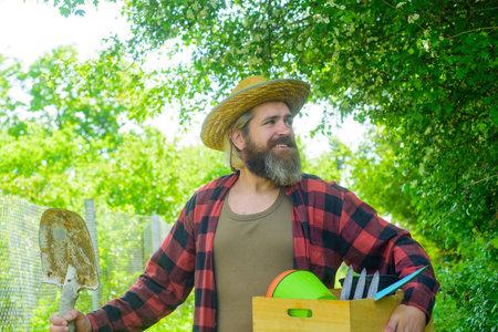 Bearded man with gardening tools. Attractive man working in garden. Professional gardener. Gardener work. Farm. Happy bearded man in garden. Plants. Garden tools. Gardening. Eco-farm. Work in garden Stok Fotoğraf - 162233175