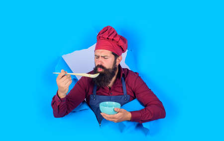 Chef man in uniform. Chef man holds wooden spoon. Healthy food. Eat healthy. Cook preparing food. Healthy ration. Advertising. Discount. Sale. Man through hole in paper