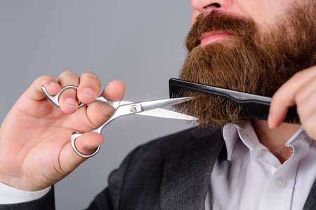 Barbershop concept. Professional beard care. Hairdresser. Salon for men. Close up portrait of bearded man with scissors and comb. Handsome bearded man with barber tools