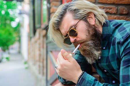Sensual man smoking outside. Tobacco. Smoking hipster. Sensual bearded man with cigarette. Cigarette smoke. Bearded man smoke the cigarette. Stylish hipster with cigarette