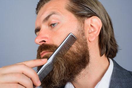 Barbershop. Professional beard care. Hairdresser. Salon for men. Close up portrait of bearded man with comb. Stok Fotoğraf
