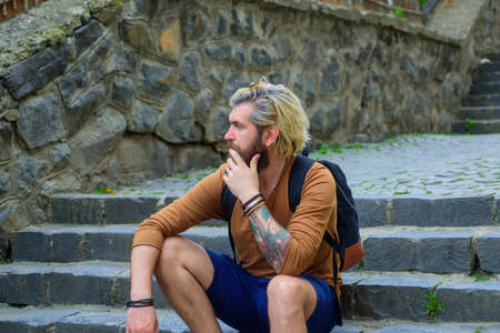 Bearded man sitting on stairway, Stylish guy sitting on stairs. Handsome man outdoors. Male barbershop style. Dyed and healthy hair. Bearded man relax outdoor