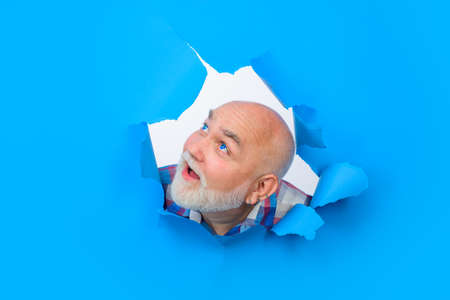 Advertising. Man through hole in blue paper. Surprised bearded man making hole in paper. Attractive man looking through hole. Copy space for advertising, to insert text or slogan. Discount. Sale