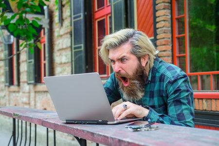 Online gaming. Winning online. Excited man with laptop outdoors. Online work. Digital work. Freelance. Online casino. Playing poker. Money game. Surprised man with laptop Standard-Bild
