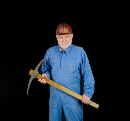Man holding pick-ax. Male miner worker in coveralls with pickaxe. Construction and building works. Bearded man in uniform holds pick ax. Builder man holds pickaxe. Craftsman working with pickaxe