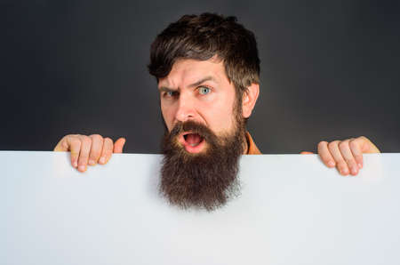 Copy space. Advertising. Confused man with blank board. Space for text. Bearded man holds empty board. Advertising banner. Handsome man shows empty board. Ready for your text or product