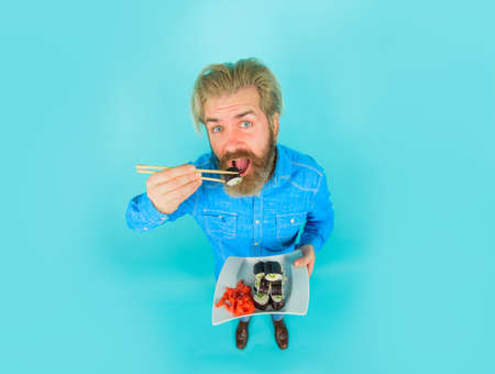 Sushi. Japan. Man eating sushi. Hipster eating sushi rolls. Sushi delivery. Japanese food. Pickled ginger. Plate of maki rolls. Susi. Exotic nutrition. Sea food 版權商用圖片