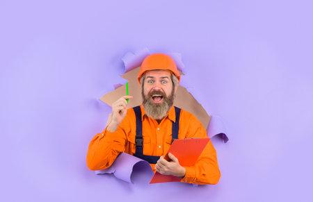 Through paper. Advertising. Repair. Building concept. Engineer making notes. Repairman with folder. Construction worker with folder. Repairman with folder. Man in hard hat. Helmet