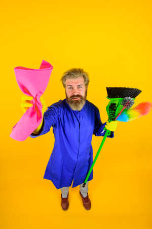 Cleaning equipment. Bearded man with rag. House cleaning. Professional cleaning. Clean up. Clearing tools. Cleaning rag. Broom. Dust brush. Household. Housekeeping. In full height 版權商用圖片