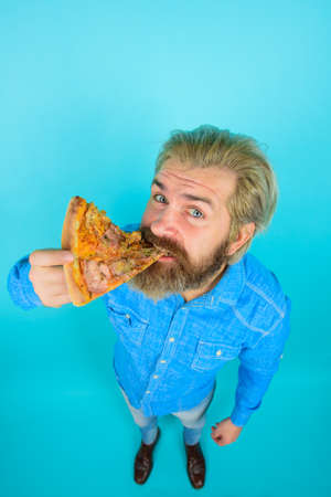 Pizza. Fastfood. Bearded man eating pizza slice. Man eat fresh pizza. Delicious fast food meal. Italian cuisine concept. Tasty pizza at restaurant. Lunch or dinner 版權商用圖片