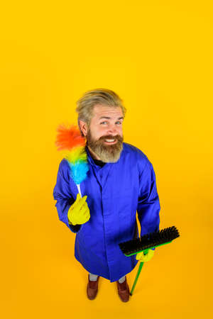 Cleaning. Clearing tools. Dust brush. Household. Housekeeping. Smiling man in uniform with dust brush. Cleaning equipment. Domestic service. Professional cleaning. Clean up 版權商用圖片