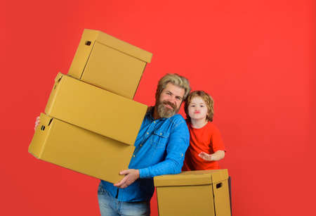 Delivery service, mail, shipment. Delivery e-commerce concept. Delivery man and boy with parcel. Kid holds cardboard box. New purchases or delivery from shop. Bearded man and little boy carry boxes