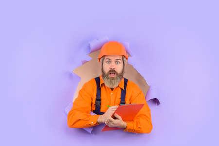 Through paper. Advertising. Repair. Building concept. Engineer making notes. Surprised repairman with folder. Construction worker with folder. Repairman with folder. Man in hard hat. Helmet 版權商用圖片