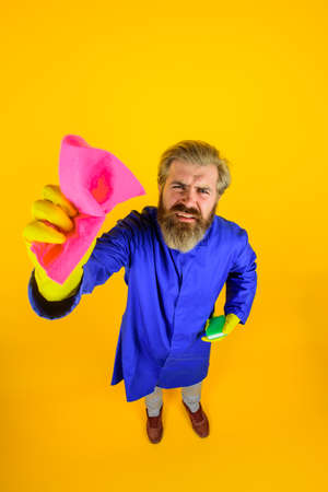 Cleaning rag. Cleaning equipment. Bearded man with rag. House cleaning. Professional cleaning. Clean up. Clearing tools. Household. Housekeeping. Full height