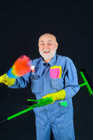 Dust. Cleaning. Man with cleaning tools. Bearded man in uniform with broom and scoop. Household. Housekeeping. Besom. Broom. Disinfection. Professional cleaning. Cleaning service. Clean up 版權商用圖片