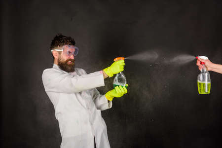 Bearded man with cleaning equipment. Cleaning advertising. Cleaners. Cleaning service. Bearded man with cleaning spray. Bearded man in uniform and rubber gloves holds cleanser spray 版權商用圖片