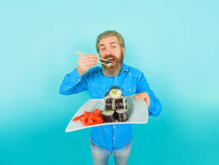 Sushi rolls. Japanese cuisine. Japan meal. Sushi roll. Man eat sushi with chopsticks. Japanese culture. Bearded hipster eating rolls. Japanese food delivery. Pickled ginger with sushi or sashimi