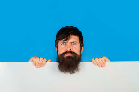 Copy space. Advertising. Bearded man with blank board. Space for text. Man holds empty board. Advertising banner. Man shows empty board. Ready for your text or product.