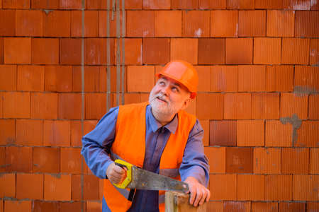 Construction worker sawing with hand saw. Handyman with hand-saw. Carpentry work. Builder worker carpenter handyman with saw. Wood sawing with handsaw. Carpentry service. Builder Sawing with hand saw