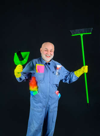 Cleaning. Clearing tools. Bearded man in uniform with broom and scoop. Household. Housekeeping. Besom. Broom. Cleaning and disinfection. Professional cleaning. Cleaning service. Clean up