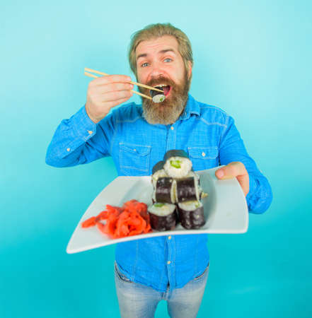Sushi. Man with sushi in chopstick. Japan. Hipster eating sushi. Sushi delivery. Japanese food. Pickled ginger. Plate of maki rolls. Susi. Exotic nutrition. Sea food. Full height. Copy space 版權商用圖片