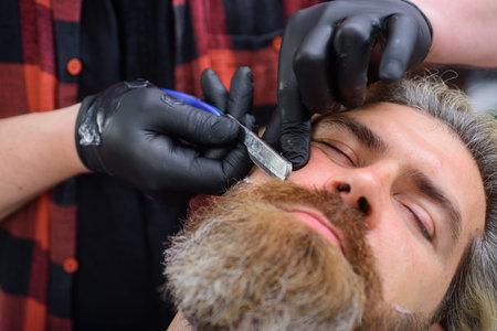 Barbershop procedures. Professional beard care. Hairdresser. Salon for men. Barber-shop. Close up portrait of bearded man with razor. Handsome bearded man with hairdresser or barber tools