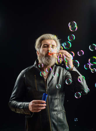 Soap bubbles. Play with bubbles. Bearded man blowing soap bubbles. Happiness. Good mood. Childhood