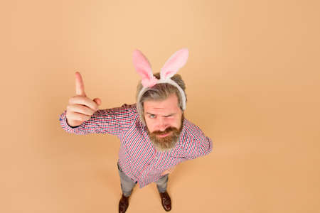 Easter man points finger on copy space. Sale. Discount. Season sales. Happy Easter. Man in bunny ears. Rabbit man. Man in rabbit ears. Springtime. Holidays. Preparation for Easter