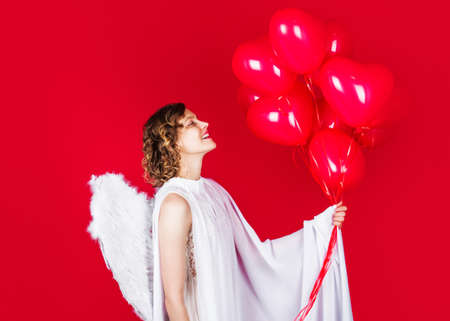 Valentines Day. Cupid angel with balloons. Female with white wings.