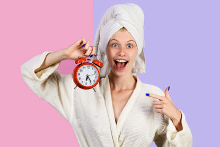 Smiling morning woman with alarm clock. Happy girl in bathrobe with alarm watch. Woman pointing on alarm-clock. Time concept. 版權商用圖片