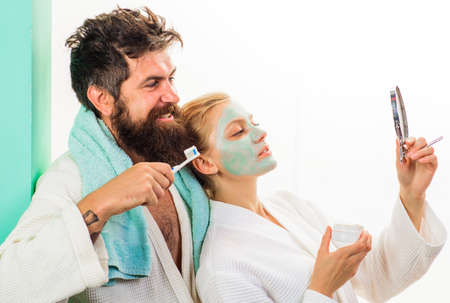 Couple In bathroom. Morning Family life. Wife with cosmetic facial mask, husband with with toothbrush cleaning teeth.