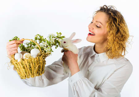 Smiling easter woman with white rabbit and basket with eggs. 版權商用圖片