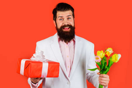 Handsome man with gift and flowers. Businessman with bouquet of tulips and present for birthday. Romantic guy. Valentines Day, Womens Day. 版權商用圖片